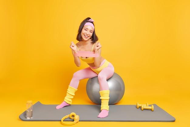Mulher usa acessórios esportivos treina os músculos dos braços com banda de resistência senta na bola de fitness vestida com roupas esportivas