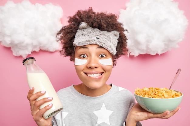 Mulher usa adesivos de máscara de dormir de pijama sob os olhos segura uma tigela de cereais e leite contém poses nutritivas para o café da manhã dentro de casa