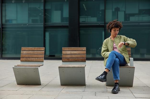 Mulher usa aplicativo em smartwatch moderno para organizar o tempo verificado notificação recebida usa gadget vestível ouve música em fones de ouvido