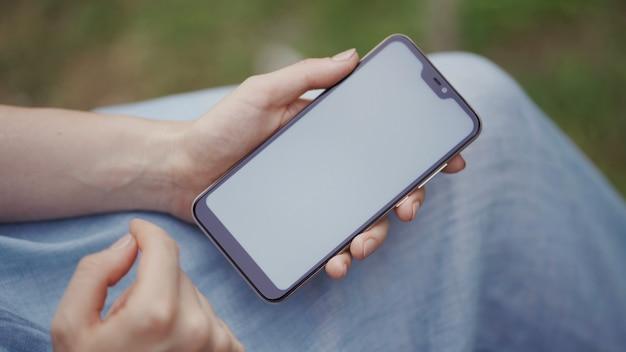Mulher usa as mãos digitando em telefones celulares e tela de toque, trabalhando com dispositivos de aplicativos de estilo vintage no parque