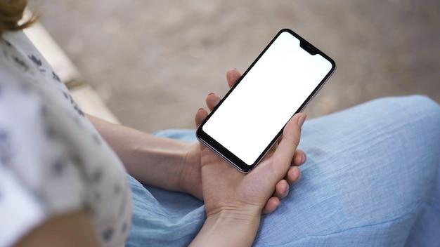 Mulher usa as mãos digitando em telefones celulares e tela de toque, trabalhando com dispositivos de aplicativos de estilo vintage no parque Foto Premium