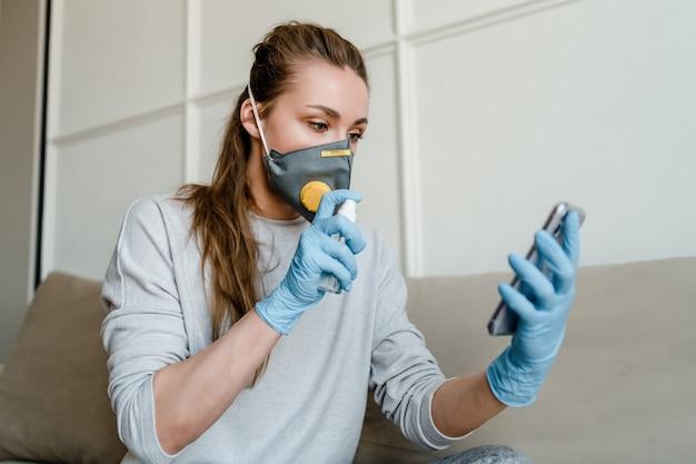 Mulher usa desinfetante para as mãos no telefone em casa usando máscara respiratória e luvas médicas