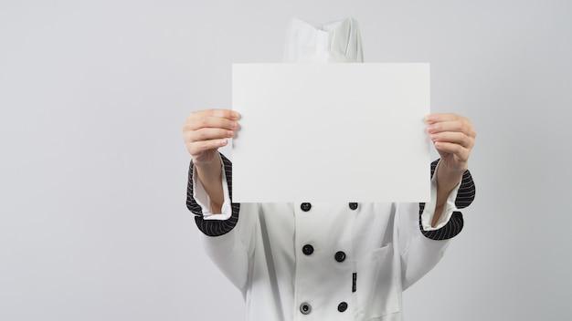 Mulher usa jaqueta de cozinheiro e chapéu de chef e segurando papel a4 em fundo branco.