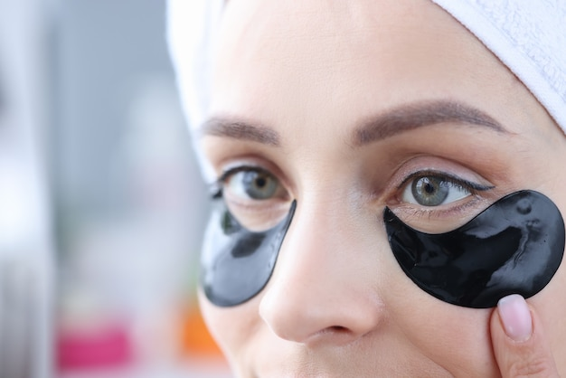Mulher usa manchas pretas embaixo dos olhos para eliminar o inchaço e suavizar as rugas