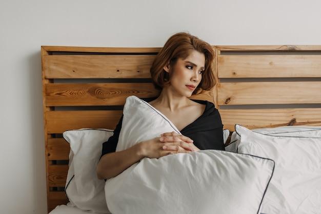Mulher usa maquiagem completa e relaxa na cama. conceito de solidão.