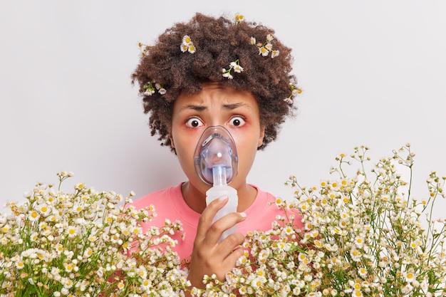 Mulher usa máscara de nebulizador para respirar olhares livres impressionada tem olhos vermelhos reação alérgica a poses de camomila em ambientes fechados em branco