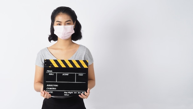 Mulher usa máscara facial e mãos segurando claquete ou filme preto sobre fundo branco
