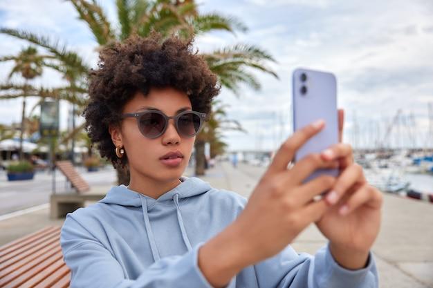 Mulher usa óculos escuros e moletom azul faz selfie em poses de câmera do smartphone perto do porto marítimo poses fora faz ligação online usa internet grátis