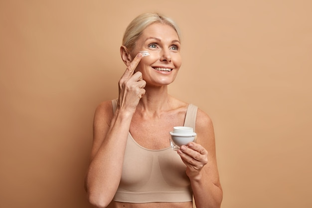 Mulher usa produto de beleza aplica creme facial nutritivo para hidratar a pele concentrada com expressão sonhadora
