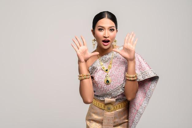 Mulher usa roupas tailandesas e abre as mãos dos dois lados.