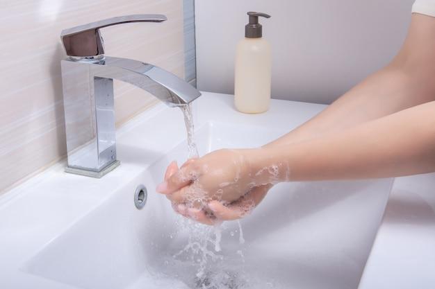 Mulher usa sabonete e lava as mãos debaixo da torneira. conceito de higiene