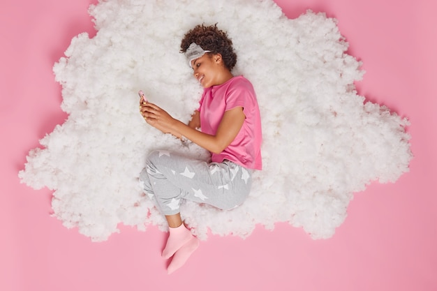 Mulher usa telefone celular lê sms em bate-papos com namorado online acorda de manhã bem-humorada vestida em poses de pijama na nuvem branca e fofa