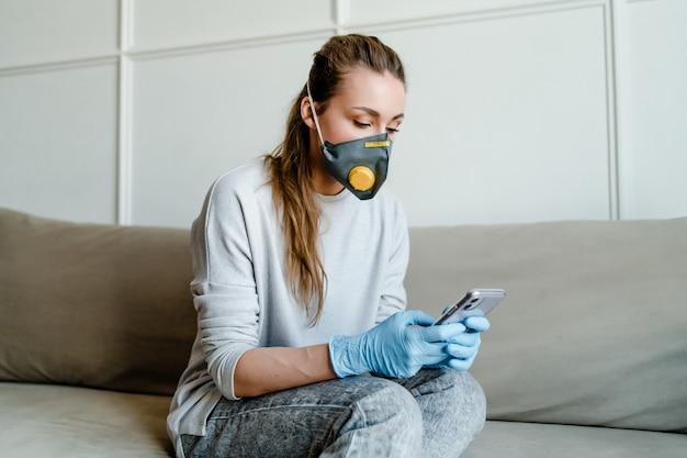 Mulher usa telefone em casa usando máscara respiratória e luvas médicas