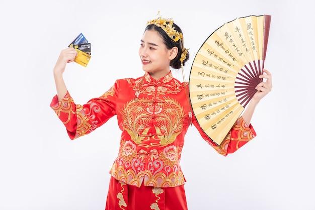 Mulher usa terno cheongsam segurando o leque chinês mostra que o cartão de crédito pode ser usado para fazer compras no ano novo chinês