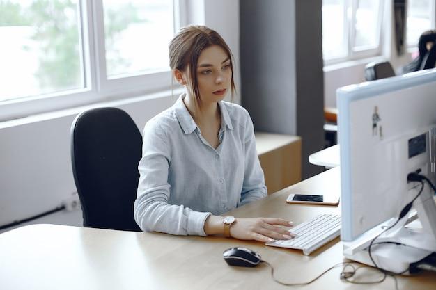 Mulher usa um computador. a menina está sentada no escritório. lady usa o teclado