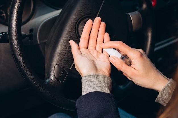 Mulher usa um desinfetante enquanto dirige um carro. precauções durante a epidemia de coronavírus. fusível de covid-19. garota com uma máscara médica em um carro.