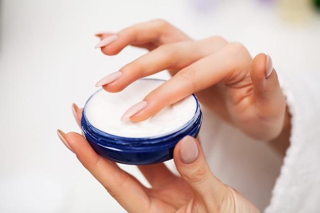 Mulher usa um hidratante para cuidar da pele