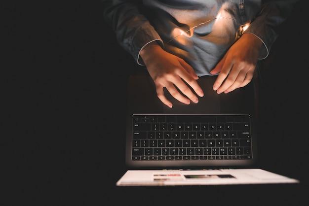 Mulher usa um laptop à noite na cama. use a internet na cama no laptop.