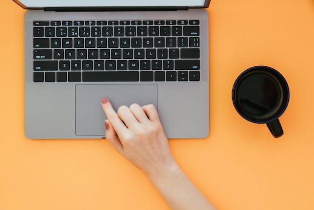Mulher usa um laptop em uma superfície laranja, uma xícara de café em cima da mesa