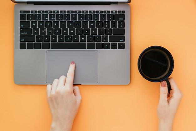 Mulher usa um laptop em uma superfície laranja