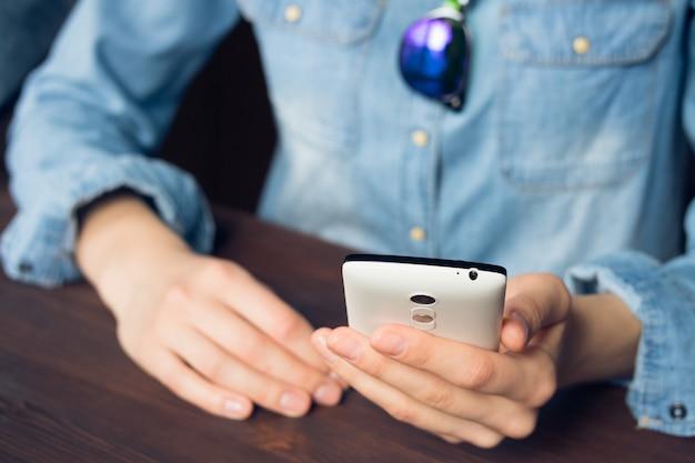 Mulher usa um smartphone, ela está vestida com uma camisa jeans e óculos de sol