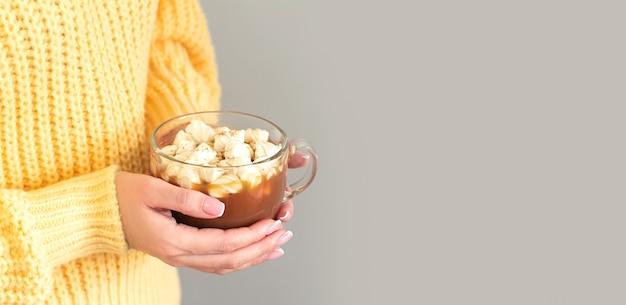 Mulher usa um suéter amarelo segurando uma caneca grande de chocolate quente ou chocolate com marshmallow