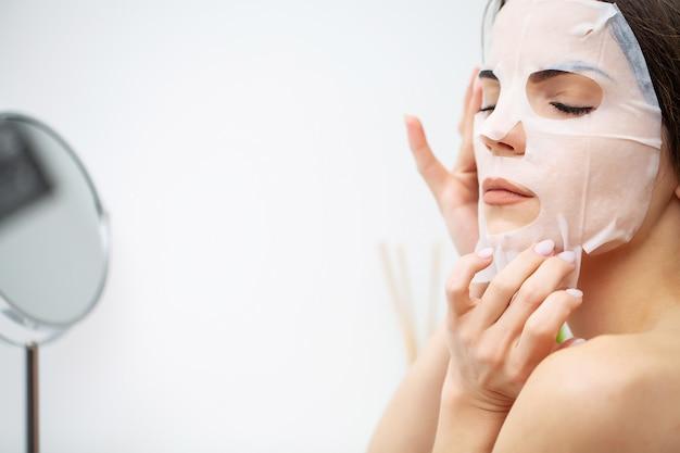 Mulher usa uma máscara hidratante para cuidar da pele