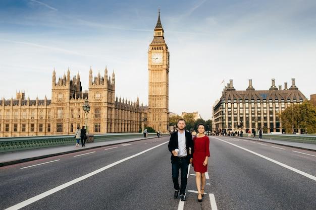 Mulher usa vestido elegante vermelho e homem de mãos dadas, passear na ponte de westminster, admirar as vistas de londres