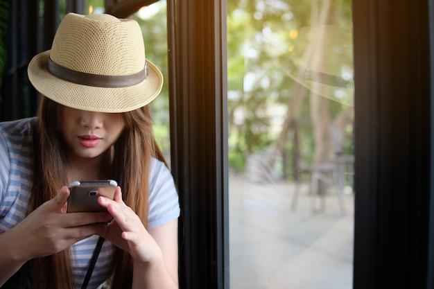 Mulher, usado, smartphone, em, loja café, ao lado, janelas