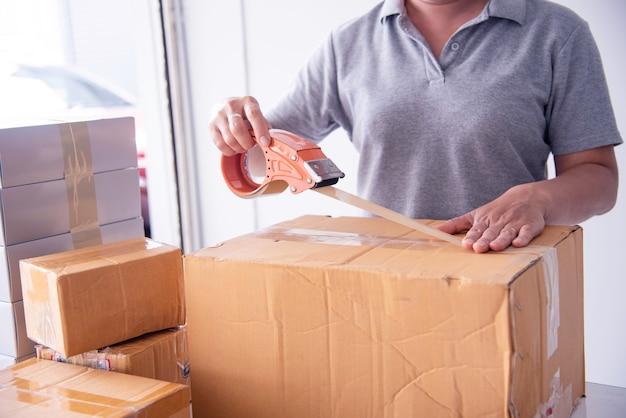 Mulher usando a fita para embalar os bens do pacote para o cliente.
