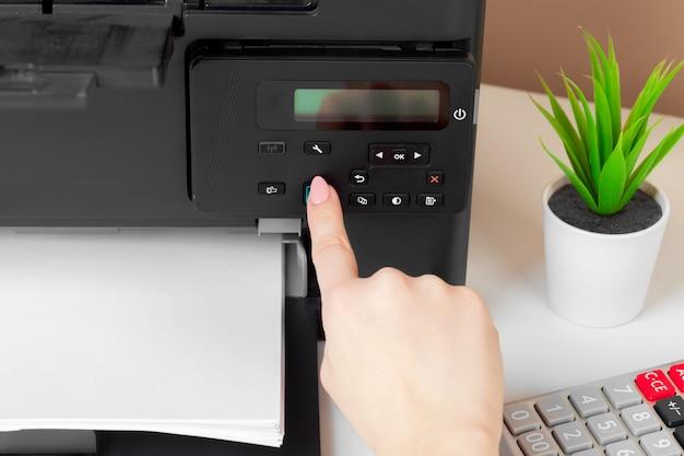 Mulher usando a impressora para digitalização e impressão de documentos