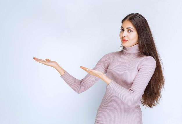 Mulher usando a mão aberta para apresentar algo ou dar uma explicação.