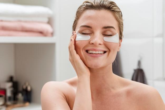 Mulher usando a redução de manchas de olheiras