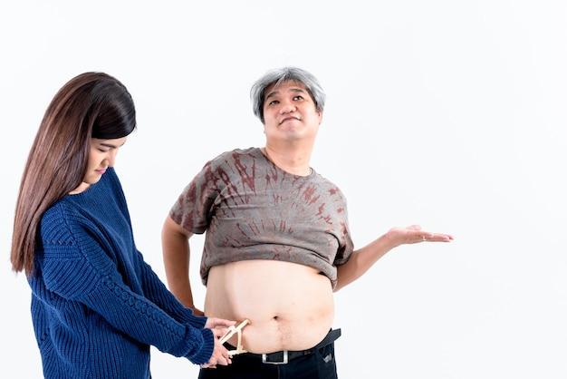 Mulher usando aparelho para medir o tamanho e a espessura do excesso de gordura na pele do homem gordo