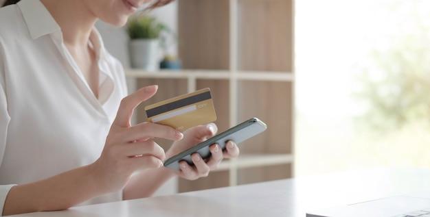 Mulher usando banco on-line com smartphone móvel com transferência de dinheiro por cartão de crédito preenchendo informações de faturamento em laptop, comprando produtos em transação de compras de pagamento em loja de comércio eletrônico