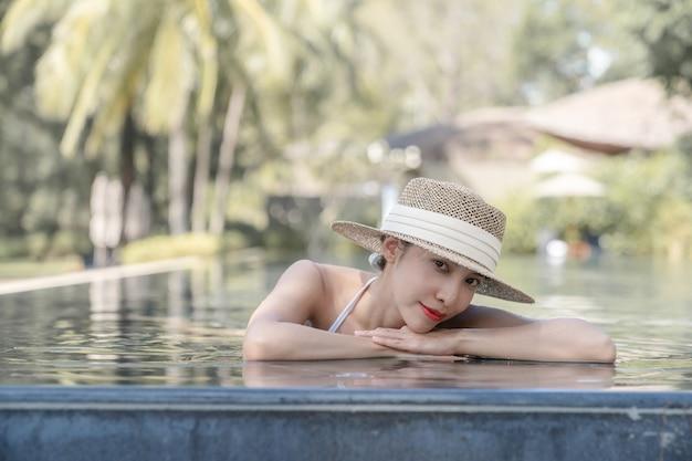 Mulher usando biquíni e chapéu de palha relaxante na piscina. conceito de tratamentos de spa.