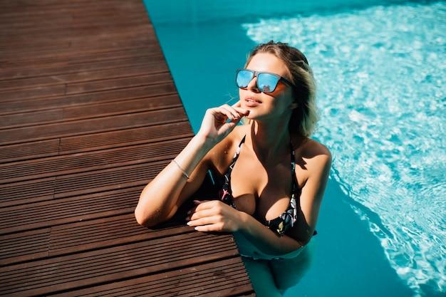 Mulher usando biquíni preto à beira da piscina em cenário de verão