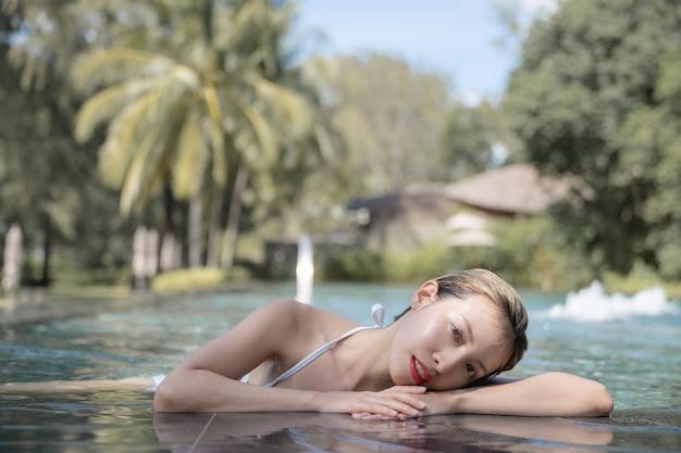 Mulher usando biquíni relaxante na piscina. conceito de tratamentos de spa.