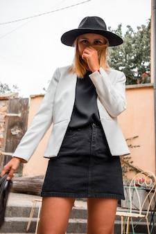 Mulher usando blazer branco e chapéu