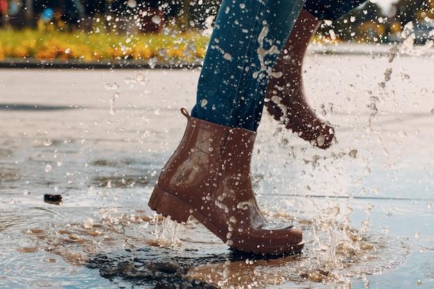 Mulher usando botas de borracha de chuva caminhando correndo e pulando em uma poça com respingos de água e gotas de chuva de outono.