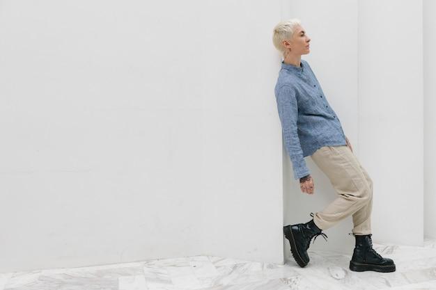 Mulher usando botas de combate casualmente parada junto a uma parede