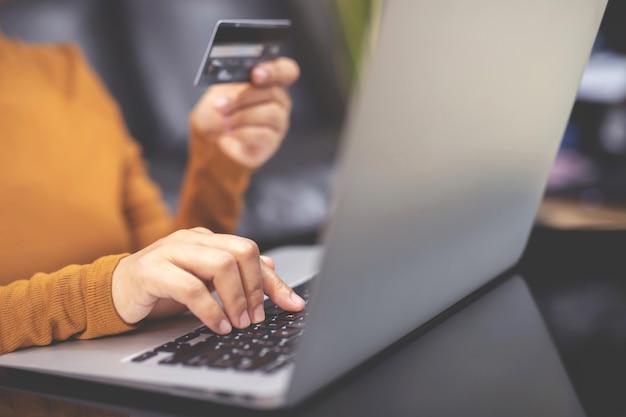 Mulher usando cartão de crédito compre online em casa