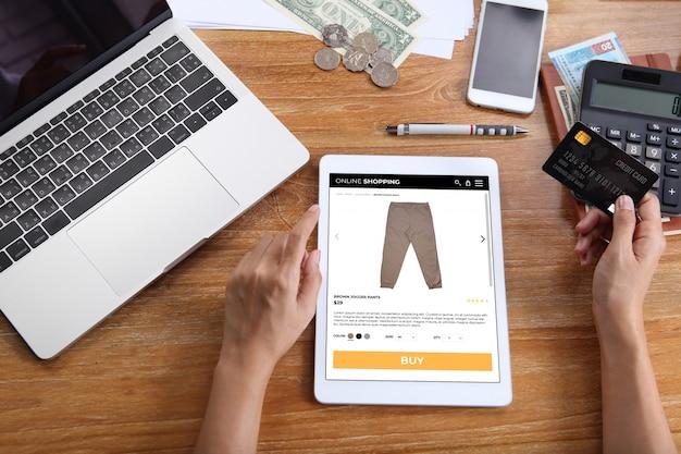 Mulher usando cartão de crédito para comprar calças de jogger marrom no site de comércio eletrônico via tablet com laptop, smartphone e escritório de papelaria na mesa de madeira