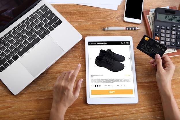 Mulher usando cartão de crédito para comprar tênis pretos no site de comércio eletrônico via tablet com laptop, smartphone e escritório de papelaria na mesa de madeira