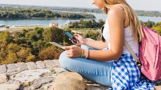 Mulher, usando, cellphone, enquanto, hiking, em, ao ar livre
