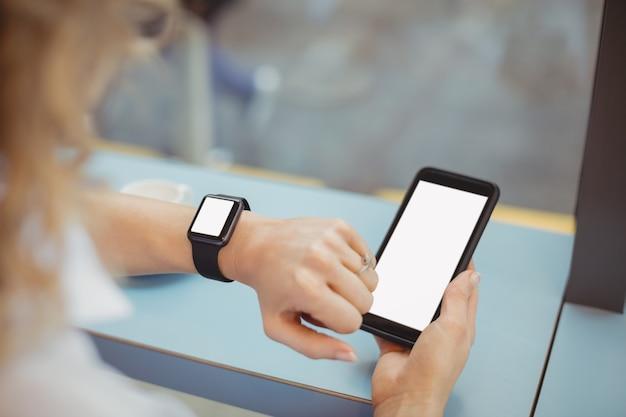 Mulher usando celular e verificando o tempo no balcão