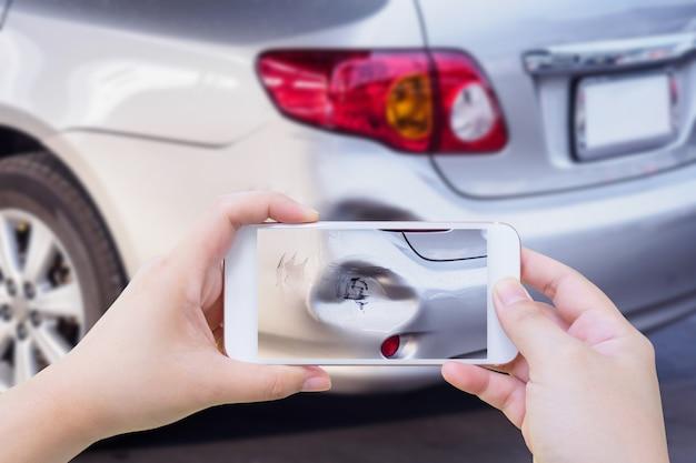 Mulher usando celular tirando foto de acidente de carro