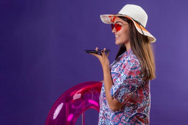 Mulher usando chapéu de verão e óculos de sol vermelhos segurando um anel inflável enviando mensagem de voz usando o telefone celular, de pé de lado com o rosto feliz em roxo