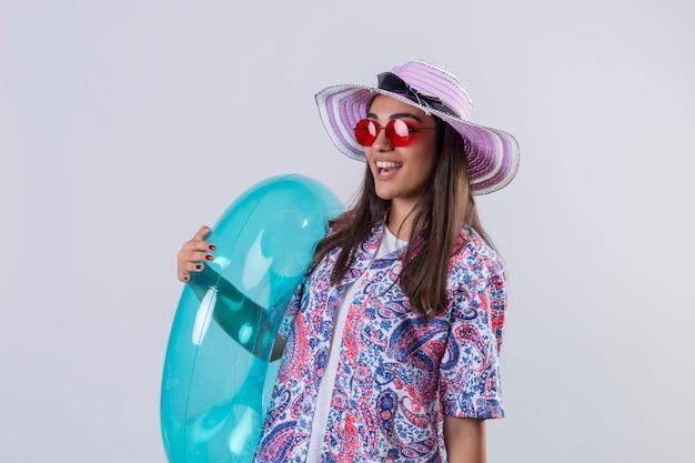 Mulher usando chapéu de verão e óculos de sol vermelhos segurando um anel inflável, parecendo alegre, positiva e feliz sorrindo alegremente em pé no branco isolado