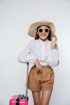 Mulher usando chapéu, óculos e alças de malas para viajar